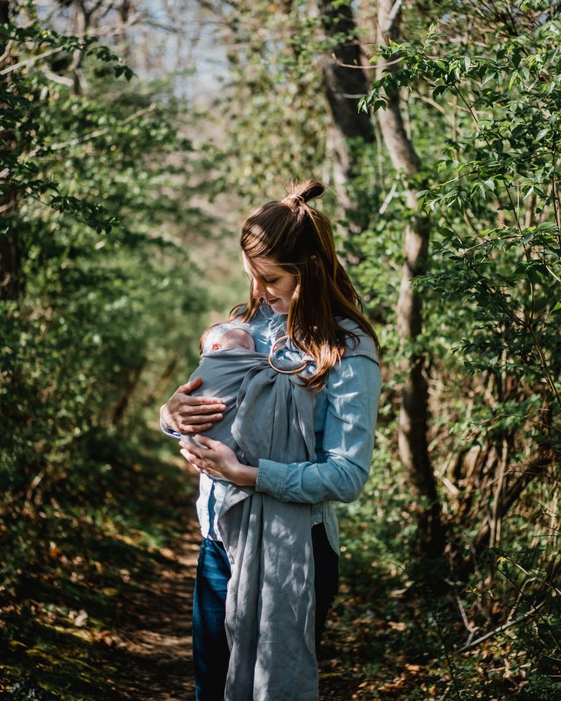 woman carrying child while standing near trees at daytime, a loving mother