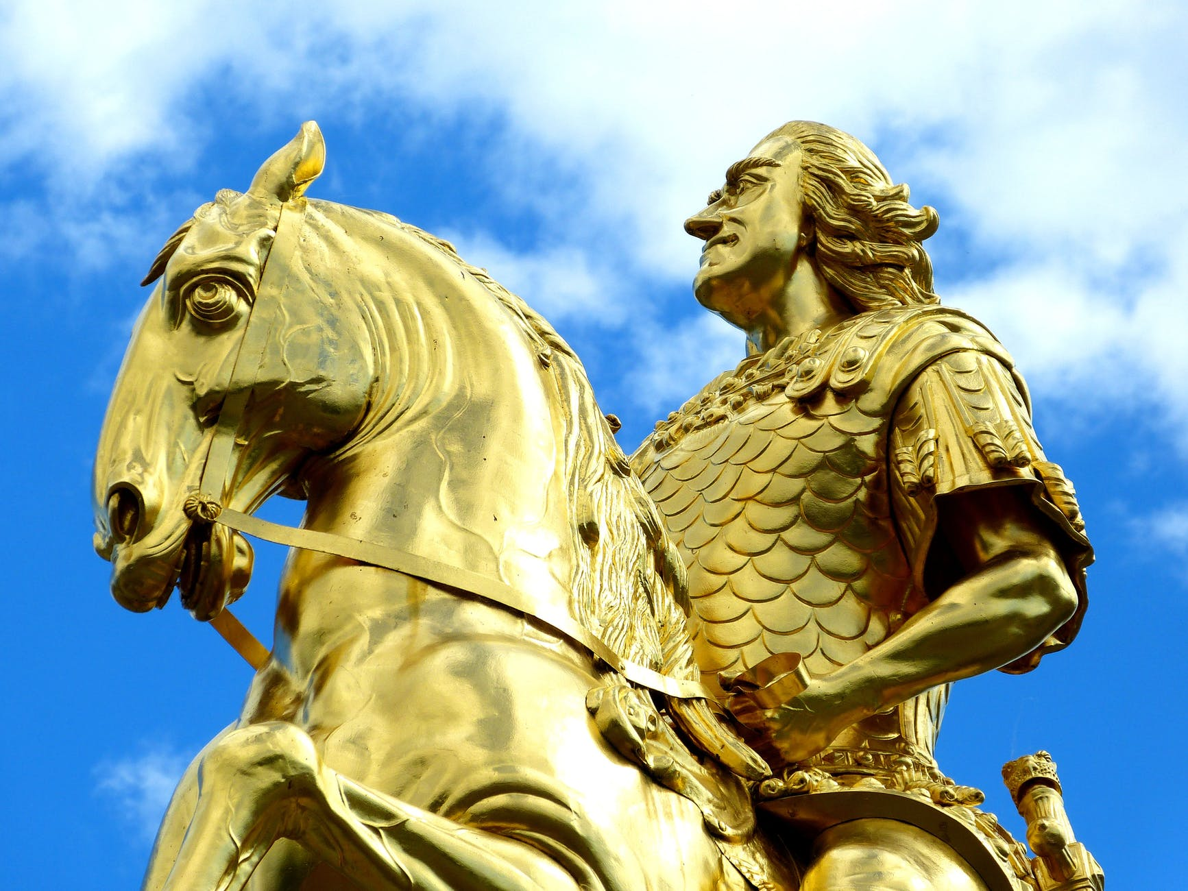golden statue under blue skies during day time