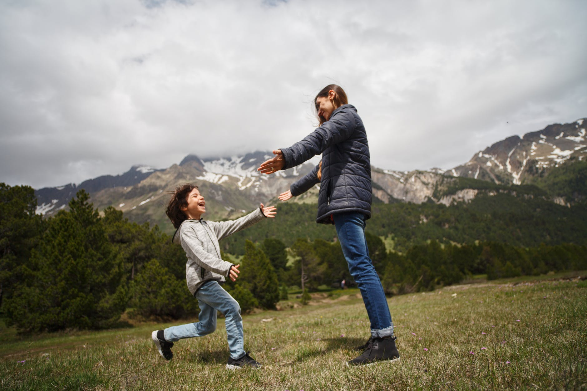 woman and child playing on green grass field near mountain