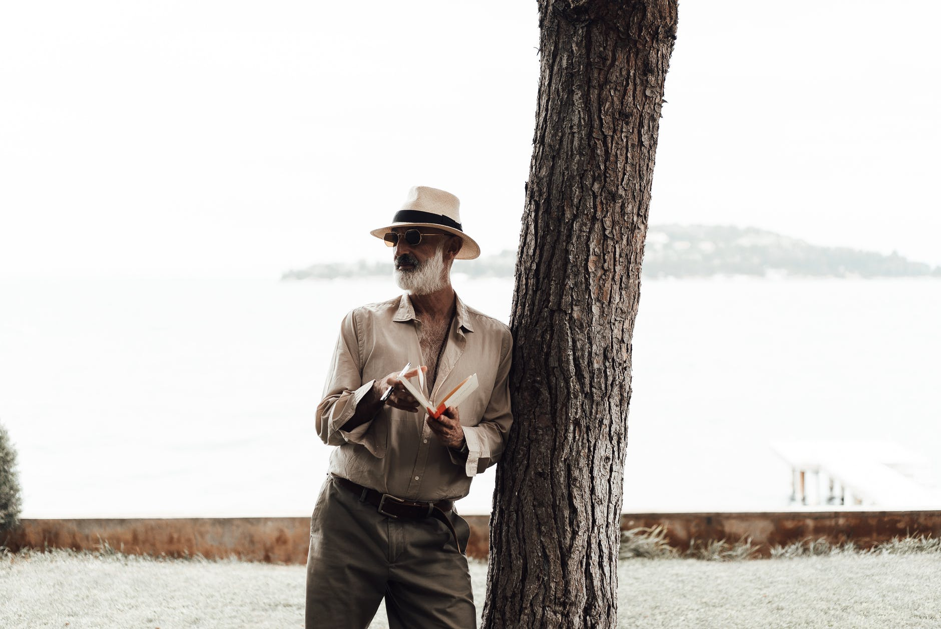 stylish mature man reading book on waterfront