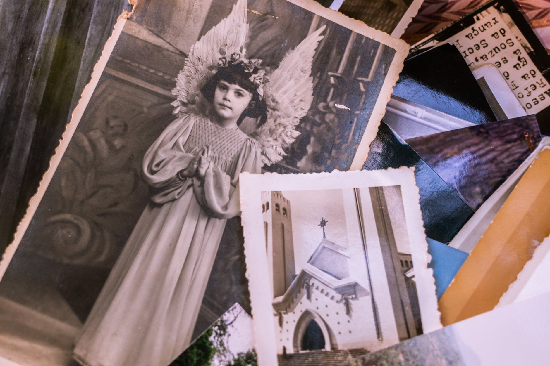 close up of old black and white photos of a young girl in an angel costume and a church